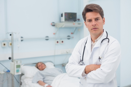 Doctor standing with crossed arms in hospital ward photo