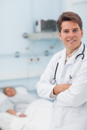 Doctor looking at camera with crossed arms in hospital ward photo