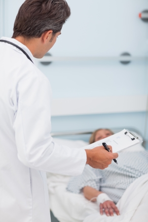 Doctor looking at his patient in a hospital ward Stock Photo - 16203171
