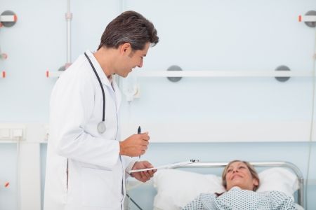 Doctor speaking with his patient in a hospital ward photo
