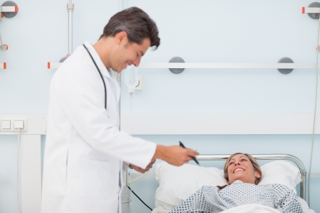 Doctor looking at his chart next to his patient in a hospital ward photo