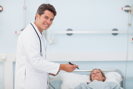 Doctor standing next to his patient in a hospital ward photo