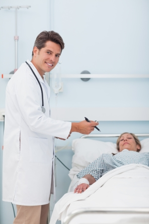 Doctor standing next to his patient while holding a chart in hospital ward Stock Photo - 16202906
