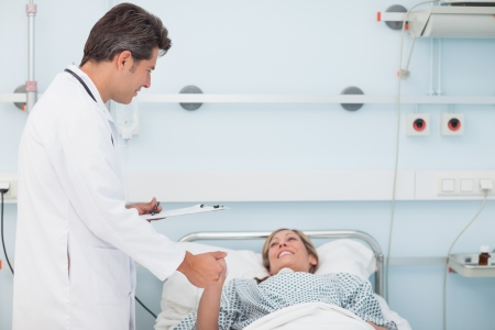 Doctor looking at his patient while holding her hand in hospital ward photo