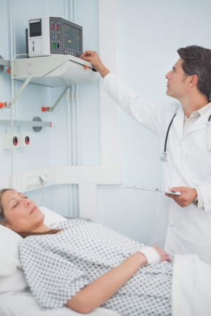 Doctor adjusting a monitor in hospital ward photo