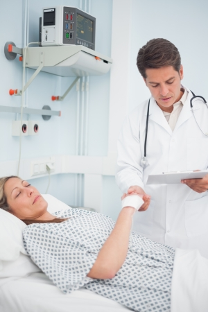 Doctor looking at his chart while holding hand of his patient in hospital ward photo
