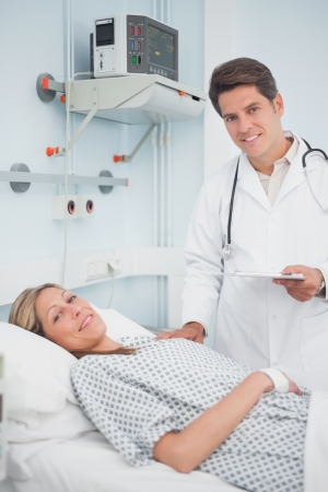Doctor and patient smiling in hospital ward Stock Photo - 16203238