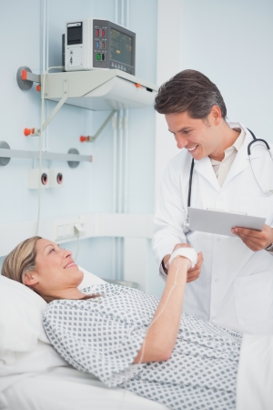 recovery bed: Medico sorridente al suo paziente in ospedale reparto Archivio Fotografico