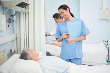 medecine: Nurse smiling to a patient in hospital ward