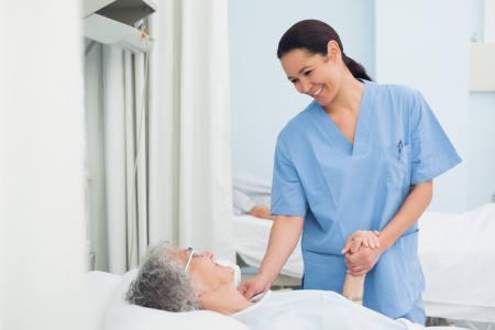 Nurse holding the hand of a patient in hospital ward photo