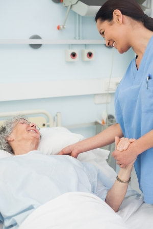 Nurse and a patient smiling in hospital ward photo