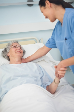 Patient smiling to a nurse while holding her hand in hospital ward photo