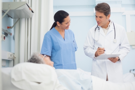 Doctor and nurse talking to a patient in hospital ward photo