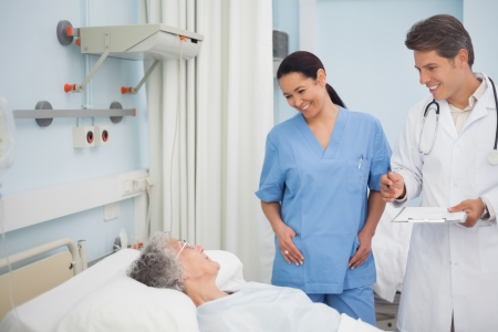 Doctor and nurse smiling to a patient in hospital ward photo