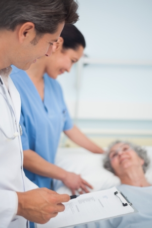 hospitalized: Doctor and nurse standing next to a patient in hospital ward