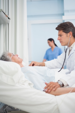 Doctor auscultating a patient with a stethoscope in hospital ward Stock Photo - 16203041
