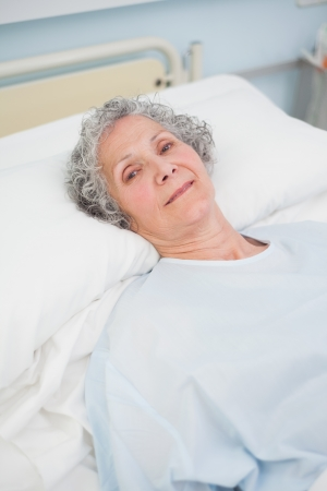 Patient looking at camera on a bed in hospital ward Stock Photo - 16202885