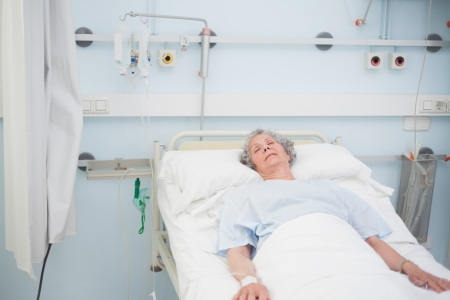 Elderly patient sleeping on a medical bed in hospital ward photo