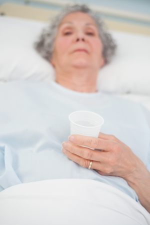 Elderly patient holding a plastic glass in her hand in hospital ward photo