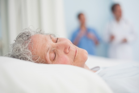 Elderly patient sleeping on a bed next to a doctor in\ hospital ward