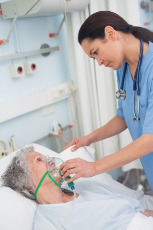 Nurse putting oxygen mask on a patient in hospital ward photo