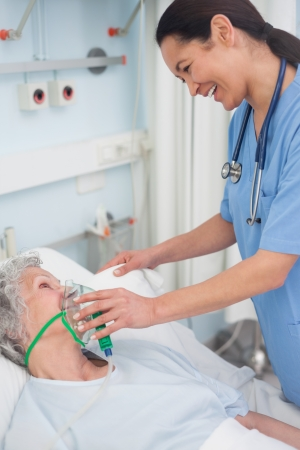 keep watch over: Nurse holding an oxygen mask in hospital ward Stock Photo