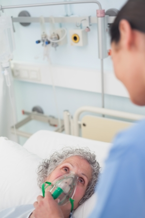 Patient having an oxygen mask on her face in hospital ward photo