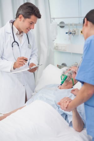 Doctor looking at patient next to a nurse in hospital ward photo
