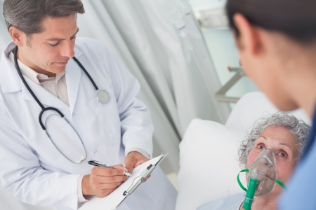 hospitalized: Doctor writing on a clipboard with a pen in hospital ward Stock Photo