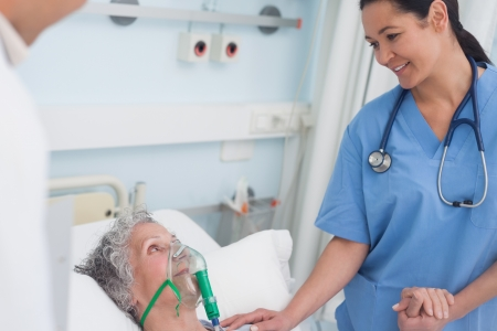 Nurse touching the hand of a patient in hospital ward Stock Photo - 16202792
