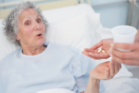 Surprised patient receiving drugs in hospital ward photo
