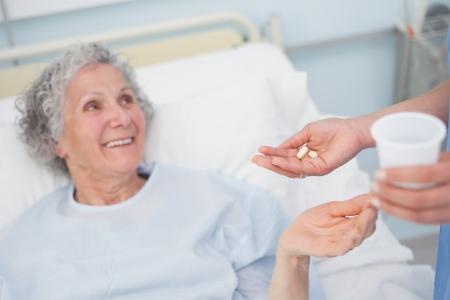 patient bed: Patient receiving drugs in hospital ward Stock Photo