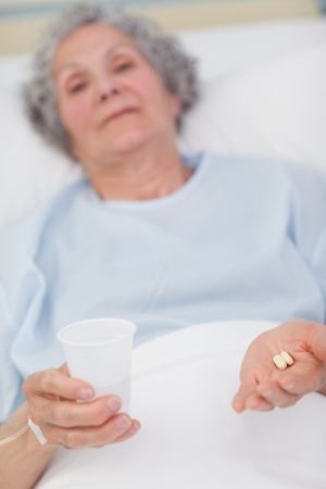 Patient holding drugs and plastic glass in her hands in hospital ward photo