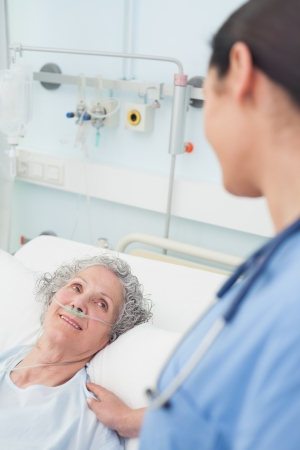 attend: Smiling patient looking at a nurse in hospital ward