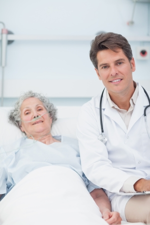 Doctor and patient on the bed looking at camera in hospital ward Stock Photo - 16202361