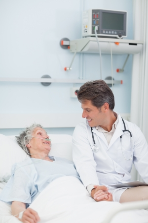 hospitalized: Doctor looking at a patient while taking her hand in hospital ward