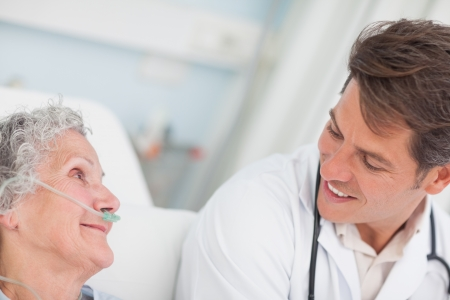 Close up of a doctor looking at a patient in hospital ward photo