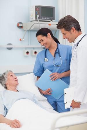 nurse clipboard: Elderly patient talking to a doctor and a nurse in hospital ward
