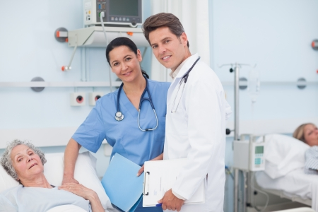 Doctor and nurse next to a patient in hospital ward Stock Photo - 16203904