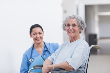 Patient in a wheelchair next to a nurse in hospital ward photo