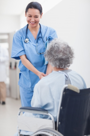 Nurse smiling while holding the hands of a patient in hospital ward Stock Photo - 16204081