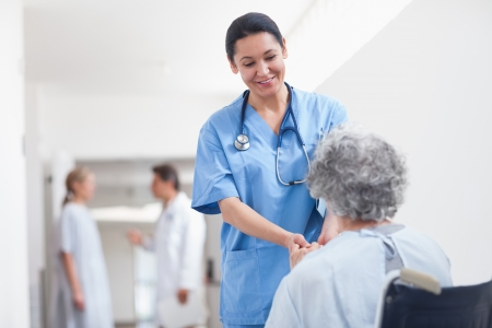 Nurse standing next to a patient while holding her hands in hospital ward Stock Photo - 16202971