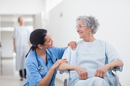 hospitalized: Elderly patient looking at a nurse in hospital ward Stock Photo