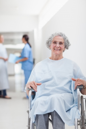 Elderly patient in a wheelchair in a corridor in hospital ward photo