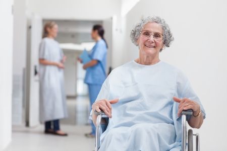 Elderly patient in corridor in hospital ward photo