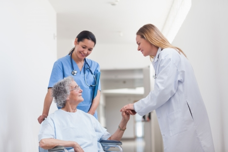 Patient in a wheelchair holding hand of a doctor in hospital ward photo
