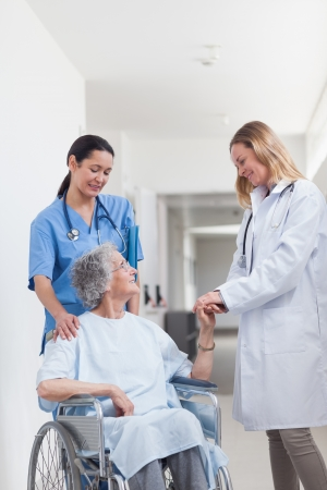 Doctor looking at a patient on a wheelchair in hospital ward photo