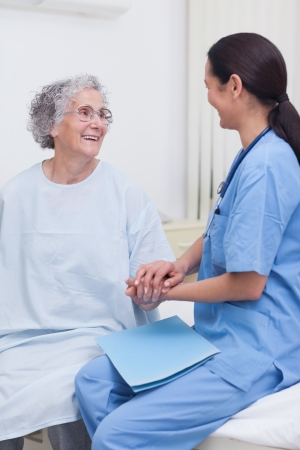 ward: Nurse sitting on bed with a patient in hospital ward