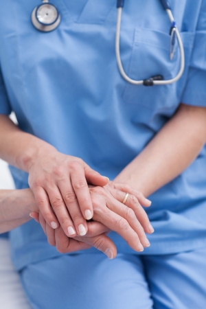 medecine: Close up of a nurse holding hand of a patient in hospital ward Stock Photo