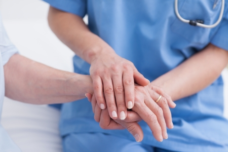 caring: Close up of a nurse touching hand of a patient in hospital ward Stock Photo